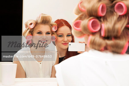 Young woman in curlers and friend taking selfie Stock Photo - Premium Royalty-Free, Image code: 649-07648653