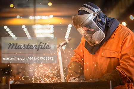 Worker grinding metal construction in marine fabrication factory Stock Photo - Premium Royalty-Free, Image code: 649-07709972