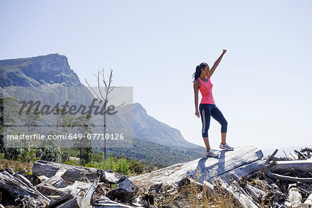 Female jogger in winning pose on hilltop Stock Photo - Premium Royalty-Free, Image code: 649-07710126