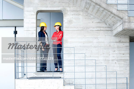 Businesswomen in safety helmet at balcony Stock Photo - Premium Royalty-Free, Image code: 649-07710139
