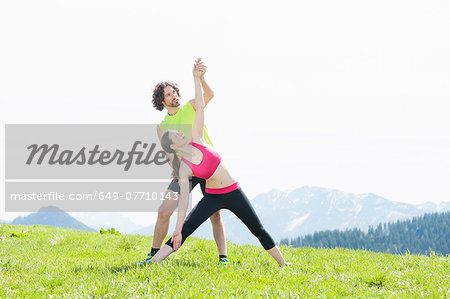 Couple practising yoga on hilltop, Wallberg, Tegernsee, Bavaria, Germany Stock Photo - Premium Royalty-Free, Image code: 649-07710143