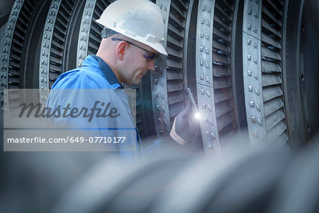 Engineer with torch inspecting turbine during power station outage Stock Photo - Premium Royalty-Free, Image code: 649-07710177