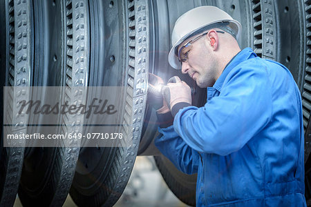 Engineer with torch inspecting turbine during power station outage Stock Photo - Premium Royalty-Free, Image code: 649-07710178