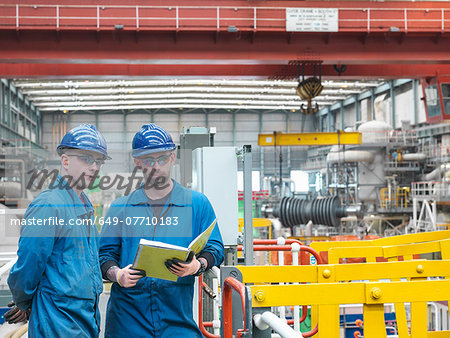 Portrait of engineers discussing notes on walkway during power station outage Stock Photo - Premium Royalty-Free, Image code: 649-07710183