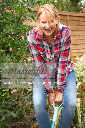 Portrait of mature woman having fun digging garden Stock Photo - Premium Royalty-Free, Image code: 649-07710279