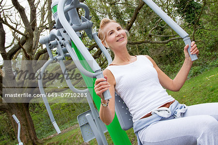 Mature woman using exercise machine in park Stock Photo - Premium Royalty-Free, Image code: 649-07710283