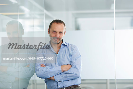 Businessman leaning against reflective wall Stock Photo - Premium Royalty-Free, Image code: 649-07710460