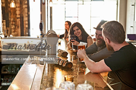 Friends drinking beer at hipster bar Stock Photo - Premium Royalty-Free, Image code: 649-07710592