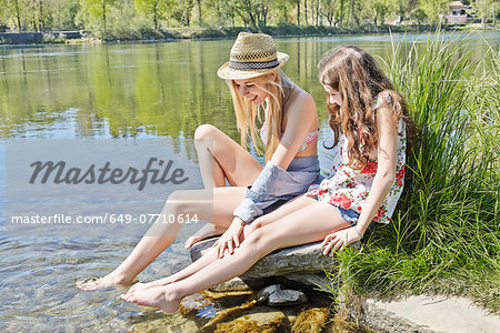 Two friends sitting on rocks by water Stock Photo - Premium Royalty-Free, Image code: 649-07710614