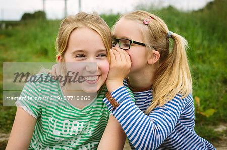 Nine year old girl whispering to sister in field Stock Photo - Premium Royalty-Free, Image code: 649-07710660