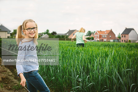 Portrait of sisters in field, one running and one posing Stock Photo - Premium Royalty-Free, Image code: 649-07710661