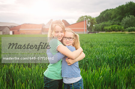 Portrait of nine year old girl and sister hugging in field Stock Photo - Premium Royalty-Free, Image code: 649-07710662