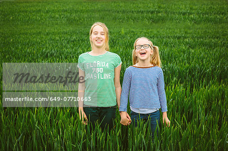 Portrait of nine year old girl and sister holding hands in field Stock Photo - Premium Royalty-Free, Image code: 649-07710663