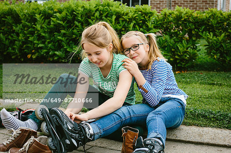 Two sisters sitting on sidewalk putting on rollerblades Stock Photo - Premium Royalty-Free, Image code: 649-07710666
