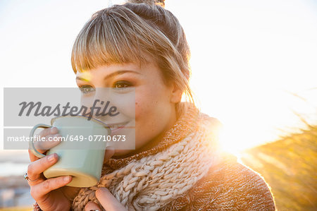 Portrait of young woman in sunlit marsh with drinks mug Stock Photo - Premium Royalty-Free, Image code: 649-07710673