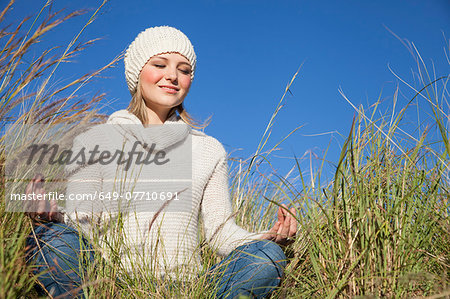 Young woman in yoga lotus position in long grass Stock Photo - Premium Royalty-Free, Image code: 649-07710691