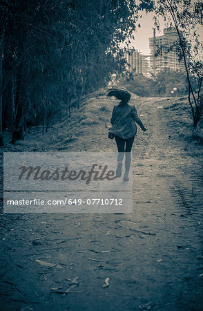Young woman running from danger up dirt track toward apartment blocks Stock Photo - Premium Royalty-Free, Image code: 649-07710712