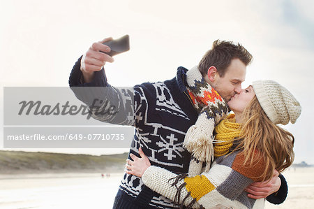 Mid adult couple taking self portrait with smartphone on beach, Bloemendaal aan Zee, Netherlands Stock Photo - Premium Royalty-Free, Image code: 649-07710735