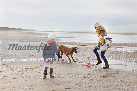 Mid adult woman with daughter and dog playing football on beach, Bloemendaal aan Zee, Netherlands Stock Photo - Premium Royalty-Free, Image code: 649-07710739