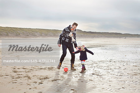 Mid adult man with daughter playing football on beach, Bloemendaal aan Zee, Netherlands Stock Photo - Premium Royalty-Free, Image code: 649-07710741