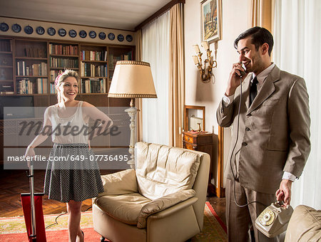 Young vintage couple in sitting room with vintage telephone and vacuum cleaner Stock Photo - Premium Royalty-Free, Image code: 649-07736495