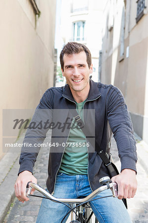Portrait of mid adult man on bicycle in city street Stock Photo - Premium Royalty-Free, Image code: 649-07736506