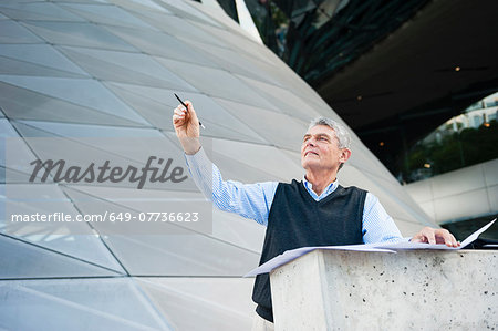 Senior adult businessman looking up, holding pen and plans Stock Photo - Premium Royalty-Free, Image code: 649-07736623