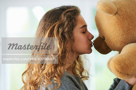 Portrait of young girl kissing teddy bear Stock Photo - Premium Royalty-Free, Image code: 649-07736667