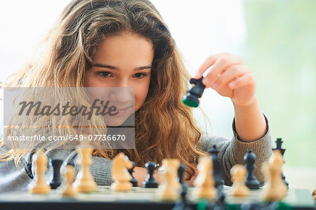 Portrait of young girl playing chess Stock Photo - Premium Royalty-Free, Image code: 649-07736670