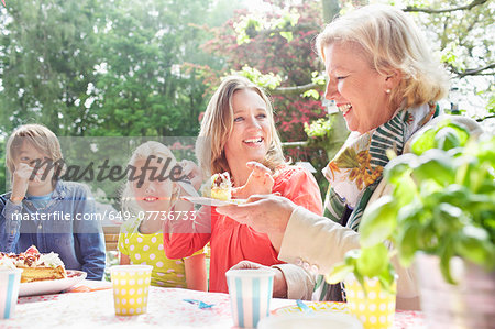 Mother serving birthday cake to family at birthday party Stock Photo - Premium Royalty-Free, Image code: 649-07736733