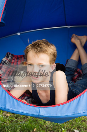 Portrait of smiling boy lying in tent suspended above grass Stock Photo - Premium Royalty-Free, Image code: 649-07736779
