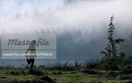 Female runner stretching by misty lake, Capel Curig, Snowdonia, North Wales, UK Stock Photo - Premium Royalty-Free, Image code: 649-07736813