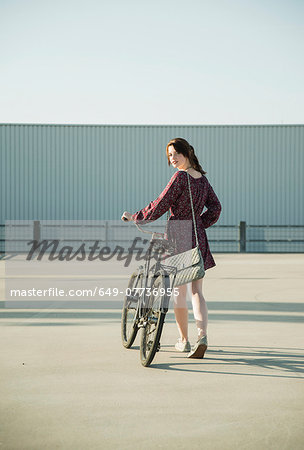 Young woman looking back whilst pushing bicycle in empty parking lot Stock Photo - Premium Royalty-Free, Image code: 649-07736955