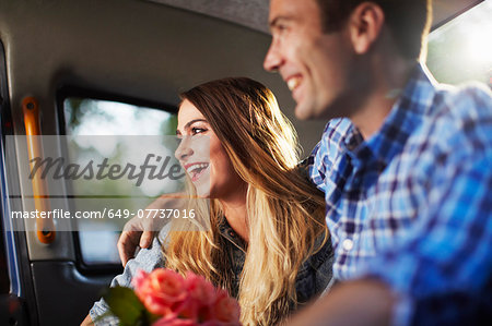 Young woman with boyfriend and bunch of roses in city taxi Stock Photo - Premium Royalty-Free, Image code: 649-07737016