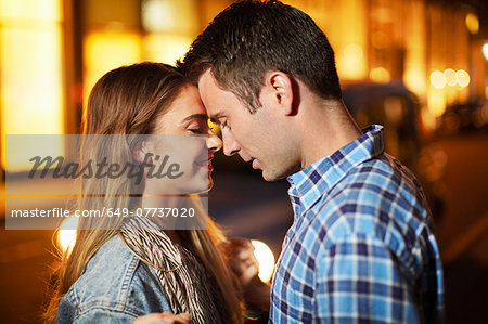 Romantic couple face to face city street at night Stock Photo - Premium Royalty-Free, Image code: 649-07737020