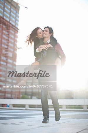 Mid adult man giving girlfriend piggyback on rooftop parking lot Stock Photo - Premium Royalty-Free, Image code: 649-07737041