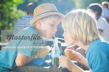 Two young boys drinking from bottle with straws Stock Photo - Premium Royalty-Free, Image code: 649-07760860
