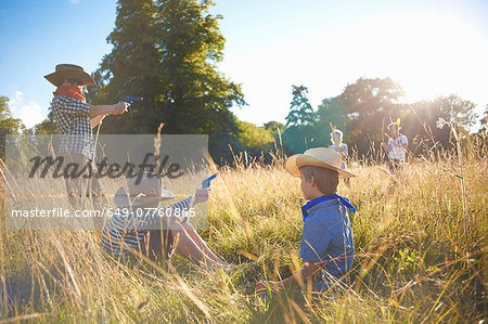 Group of young boys playing in a field Stock Photo - Premium Royalty-Free, Image code: 649-07760865