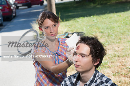 Woman cleaning man with bleeding forehead Stock Photo - Premium Royalty-Free, Image code: 649-07760997