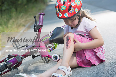 Young girl with injured leg sitting on road with bicycle Stock Photo - Premium Royalty-Free, Image code: 649-07760998