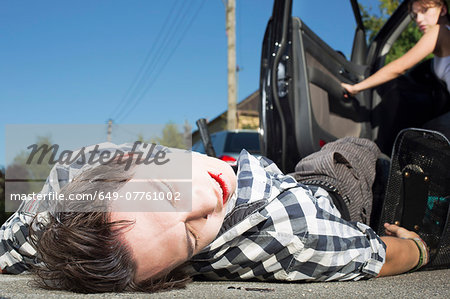 Young man hit by car lying on road Stock Photo - Premium Royalty-Free, Image code: 649-07761002
