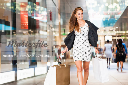 Mid adult woman walking with shopping bags Stock Photo - Premium Royalty-Free, Image code: 649-07761051