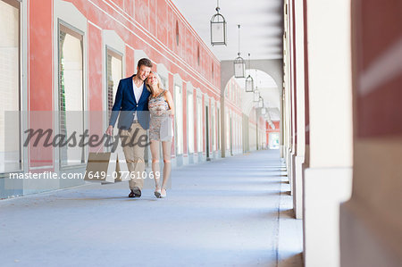 Smiling couple carrying shopping bags in city shopping mall Stock Photo - Premium Royalty-Free, Image code: 649-07761069