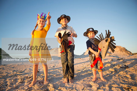 Sister and brothers dressed as native american and cowboys pointing from sand dunes Stock Photo - Premium Royalty-Free, Image code: 649-07761111