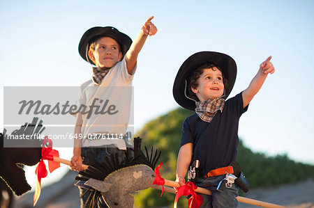Two brothers dressed as cowboys pointing from sand dunes Stock Photo - Premium Royalty-Free, Image code: 649-07761114