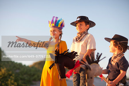 Three children dressed as native american and cowboys pointing from sand dunes Stock Photo - Premium Royalty-Free, Image code: 649-07761115