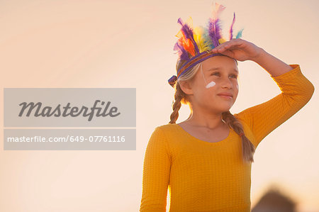 Girl dressed as native american in feather headdress with hand shading eyes Stock Photo - Premium Royalty-Free, Image code: 649-07761116