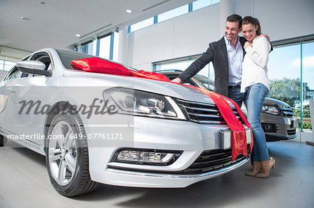 Man looking at new car with red bow with girlfriend in car dealership Stock Photo - Premium Royalty-Free, Image code: 649-07761171