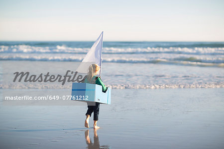 Girl running with toy boat into sea Stock Photo - Premium Royalty-Free, Image code: 649-07761212