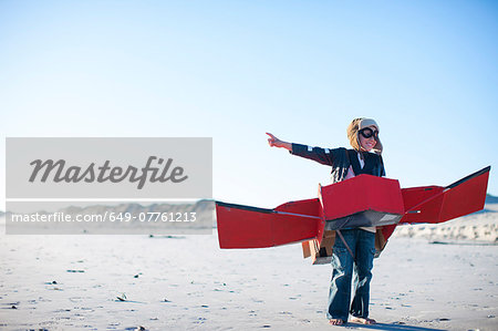 Boy standing with toy airplane and pointing on beach Stock Photo - Premium Royalty-Free, Image code: 649-07761213